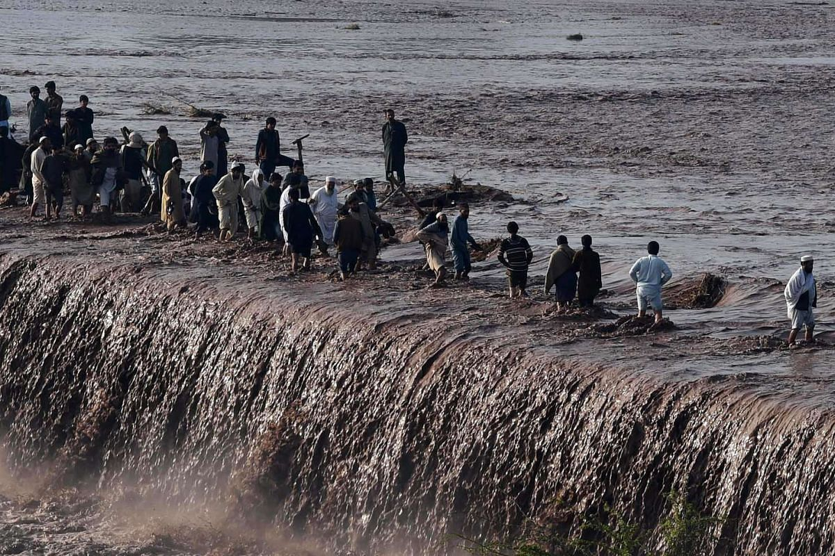 Pakistani residents crossing a flooded street, following heavy rain, on the outskirts of Peshawar on April 4, 2016.