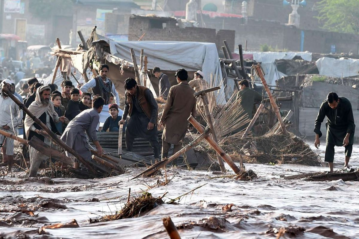 Pakistani vendors trying to salvage materials after flood water destroyed their shops following heavy rain on the outskirts of Peshawar on April 4, 2016.