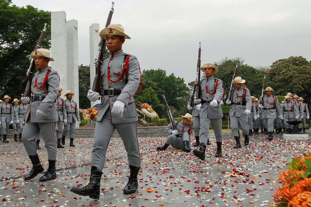 A Filipino honor guard (C, back) slips due to confetti while marching during the sunrise and wreath laying ceremony marking the start of Philippine Veterans Week at the Tomb of Unknown Soldiers inside the Heroes Cemetery in Taguig City, south of Mani
