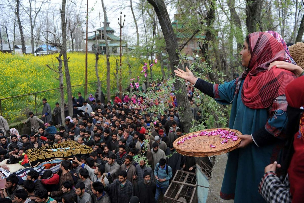 A Kashmiri woman throws sweets over the body of suspected militant Bilal Ahmed Bhat during his funeral procession in the village of Karimabad in Pulwama district, south of Srinagar, on April 6, 2016. PHOTO: AFP