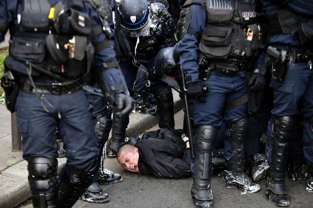 Anti-riot police officers arrest a man during clashes with high school students protesting against the government's planned labour reform, on April 5, 2016 in eastern Paris. PHOTO: AFP