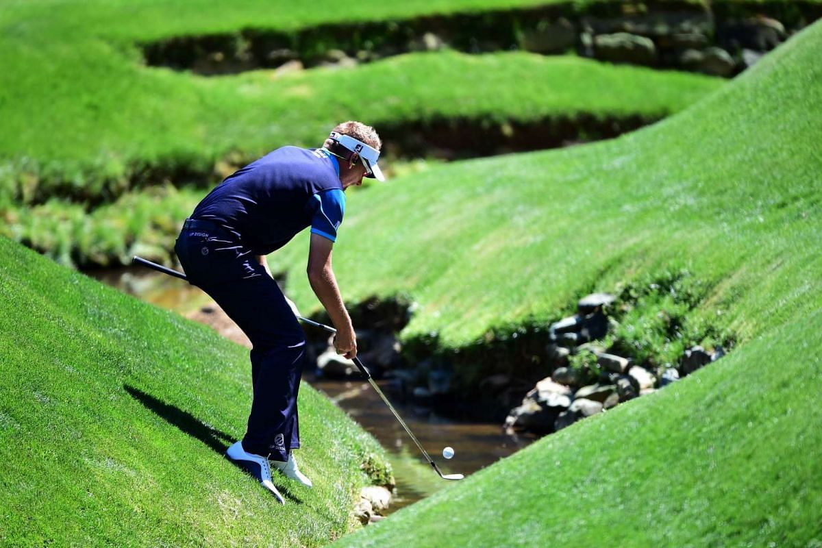 Ian Poulter of England retrieves his ball out of Rae's Creek during a practice round prior to the start of the 2016 Masters Tournament at Augusta National Golf Club on April 5, 2016 in Augusta, Georgia. PHOTO: GETTY IMAGES/AFP