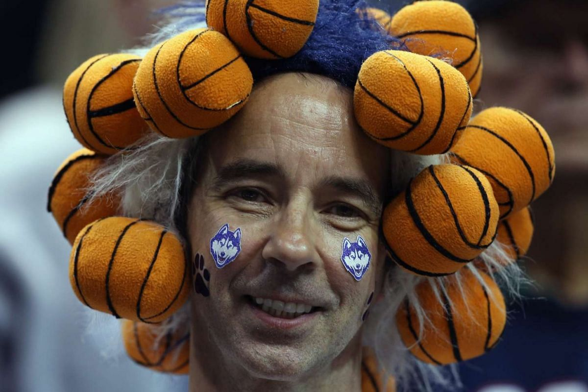 A fan wears many mini basketballs on his head in the fourth quarter between the Connecticut Huskies and the Syracuse Orange during the championship game of the 2016 NCAA Women's Final Four Basketball Championship at Bankers Life Fieldhouse on April 5