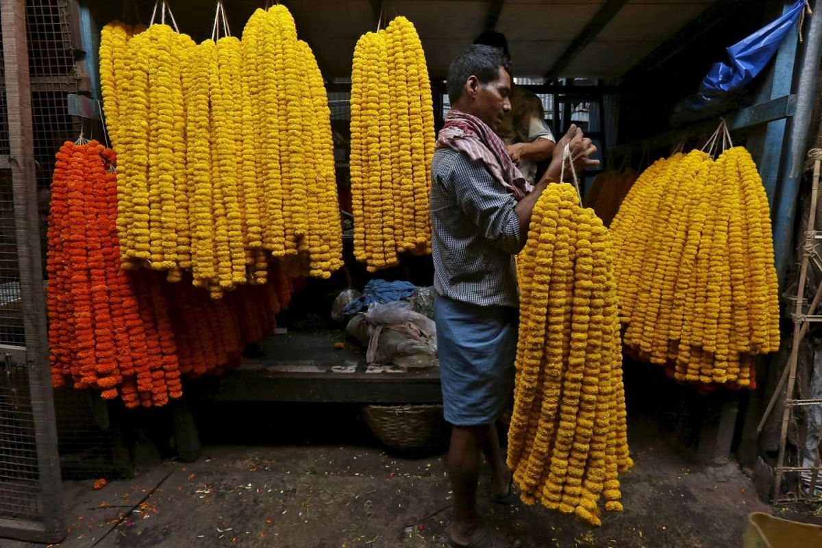 A man collects garlands of marigold flowers from a wholesale flower market for sale in Kolkata, India, April 7, 2016. PHOTO: REUTERS