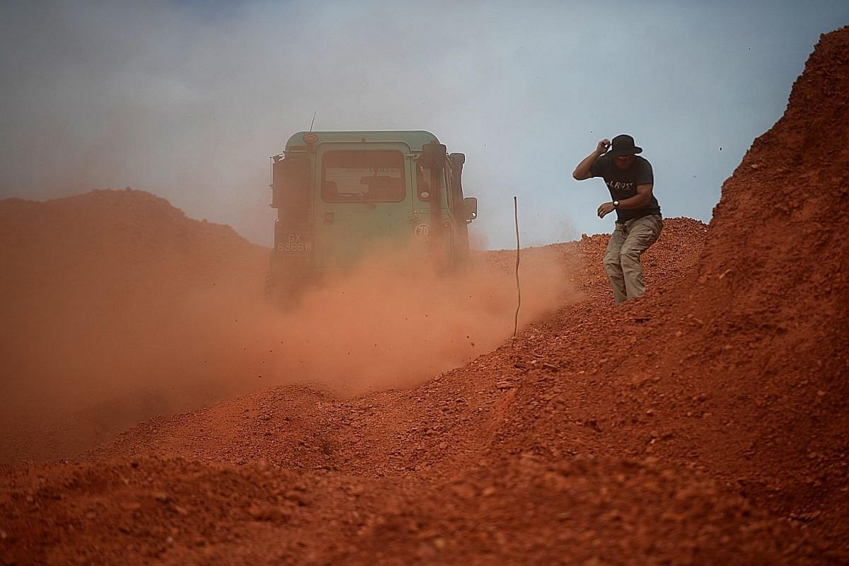 Personal trainer Gordon Ang, 33, ducking from a cloud of dust as a Defender ascends a steep slope in Desaru. A convoy of Defenders, considered one of the most rugged vehicles in the world, making their way up a rocky slope. Drivers camp on the beach