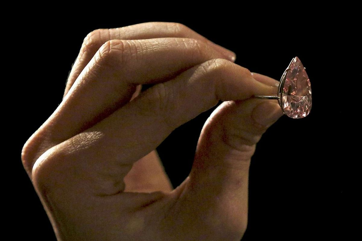 An assistant poses with a 15.38 carat vivid pink diamond at Sotheby's auction house in London, Britain on April 7, 2016.