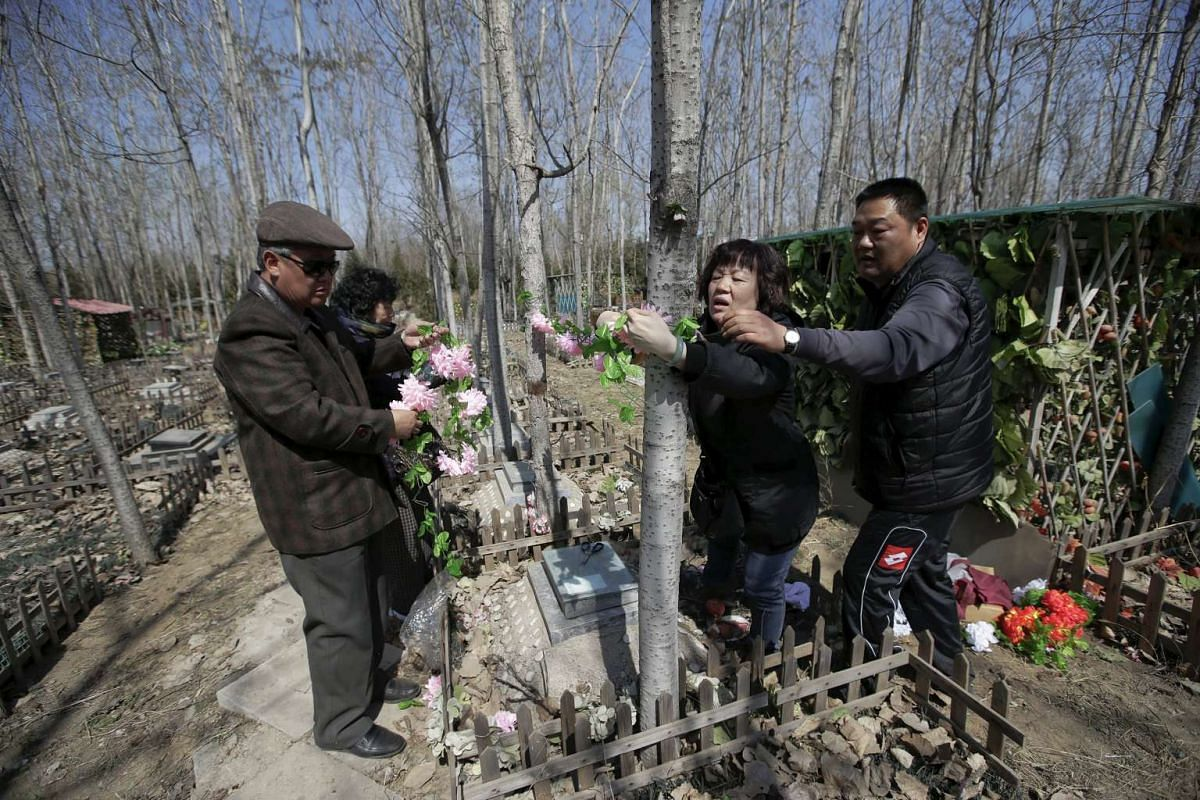A pet owner (second, right) and her relatives setting up decoration flowers for her pet dog Li Naonao at Baifu pet cemetery ahead of the Qingming Festival, also known as Tomb Sweeping Day, on the outskirts of Beijing, China, on March 26, 2016.