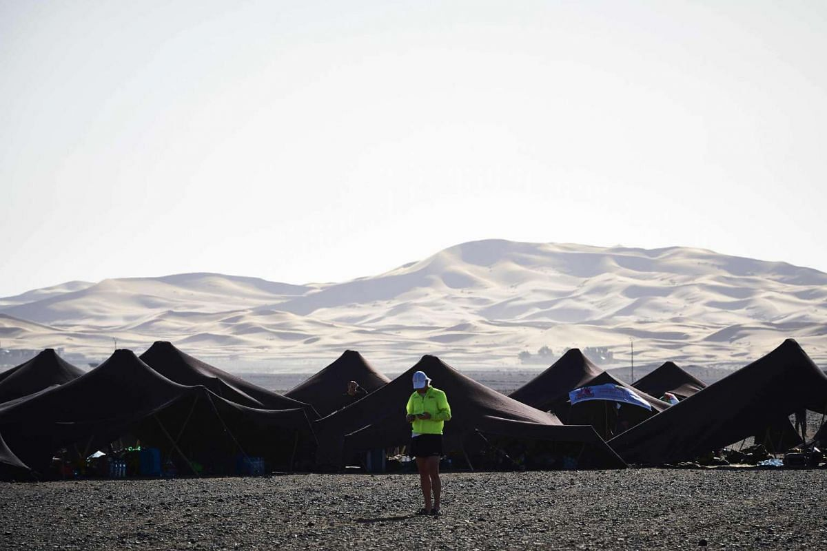 A competitor checks his phone on the eve of the 31st edition of the Marathon des Sables, on April 9, 2016.