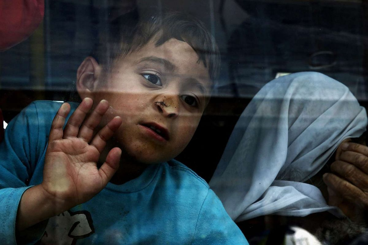 A boy looks out of a bus window as refugees from Syria and Iraq board a bus transferring them to a new organised hosting facility in Attica from the port of Piraeus, Greece, April 11, 2016. PHOTO: EPA