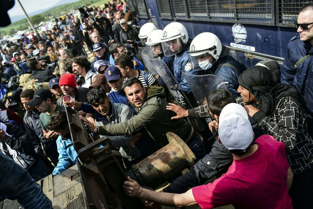 Refugees and migrants pull a wagon in an attempt to go through a barricade held by Greek police as they protest to call for the reopening of the border near their makeshift camp in the northern border village of Idomeni, on April 11, 2016. PHOTO: AFP