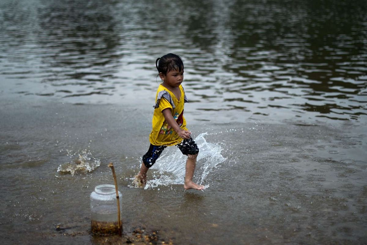 A child plays in a river to cool off as schools remain closed due to the ongoing heatwave in Termerloh, outside Kuala Lumpur, on April 11, 2016.