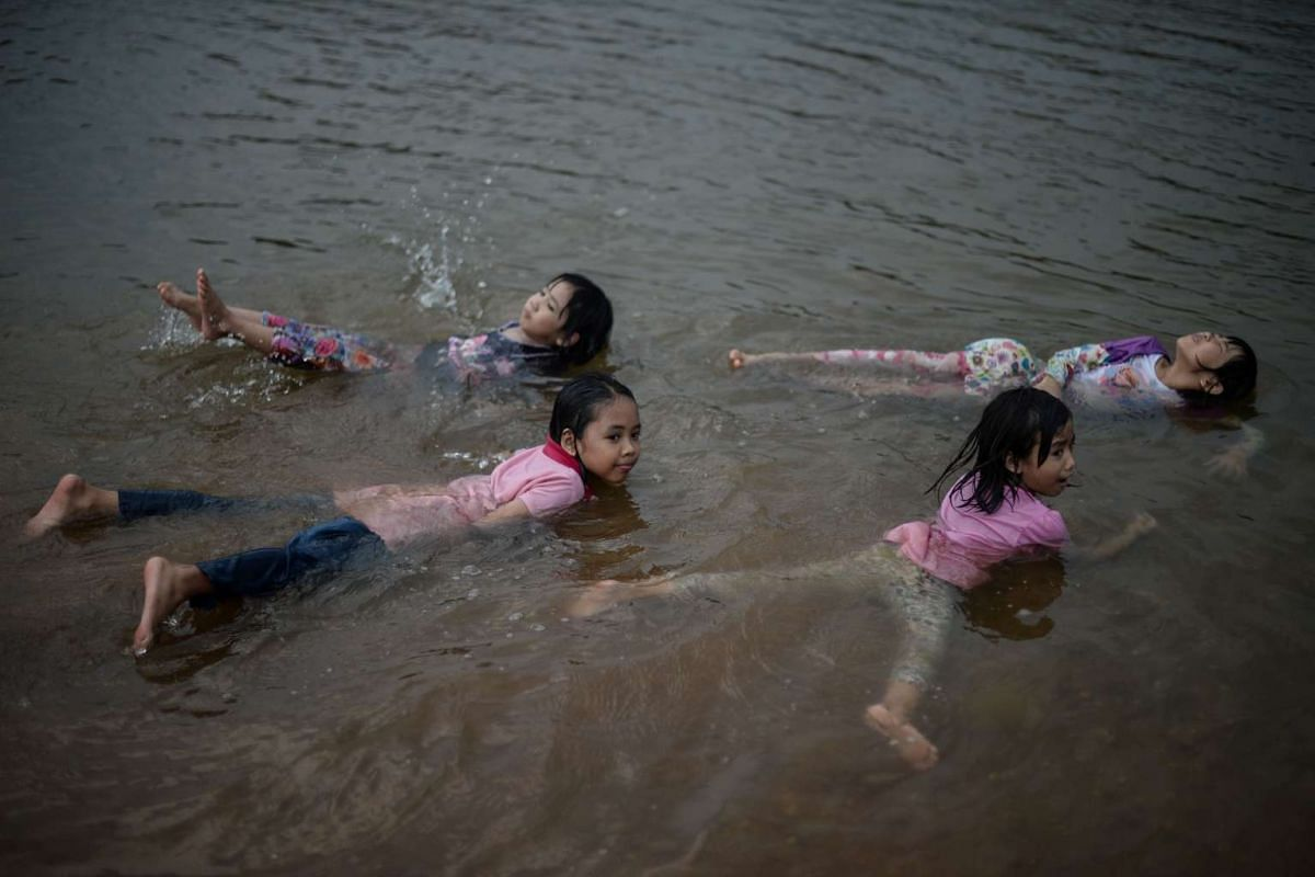 Children play in a river to cool off as schools remain closed due to the ongoing heatwave in Temerloh, outside Kuala Lumpur, on April 11, 2016.