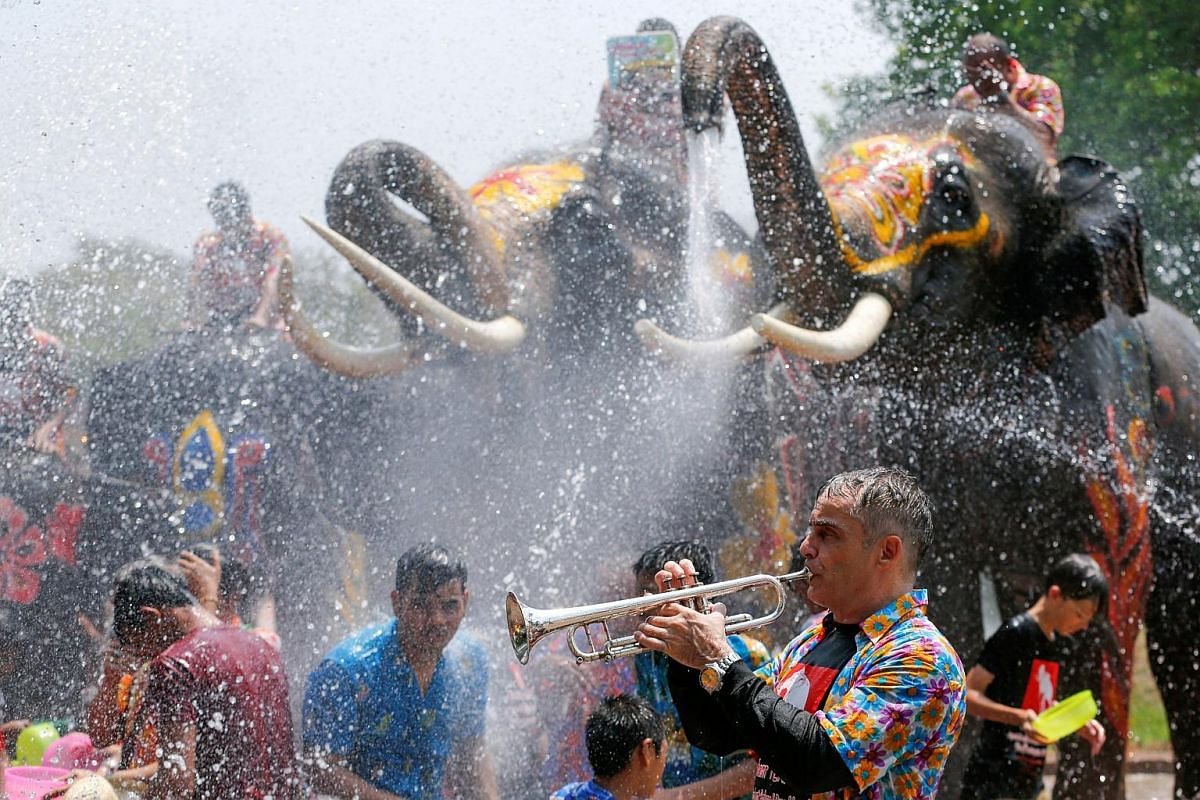 A man playing a trumpet while people are sprayed with water by elephants in Thailand's Ayutthaya province on April 11.