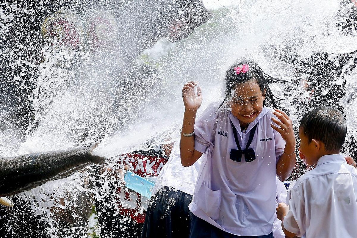 A schoolgirl is soaked with water sprayed by an elephant in Ayutthaya, Thailand, on April 11.