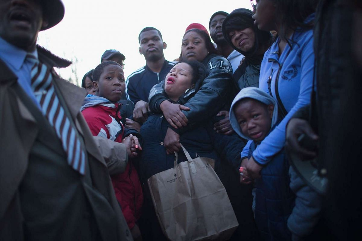 Tambrasha Hudson (centre) is comforted as she joins demonstrators protesting the shooting death of her 16-year-old son Pierre Loury near the location where he was killed on April 12, 2016 in Chicago, Illinois. PHOTO: GETTY IMAGES/AFP