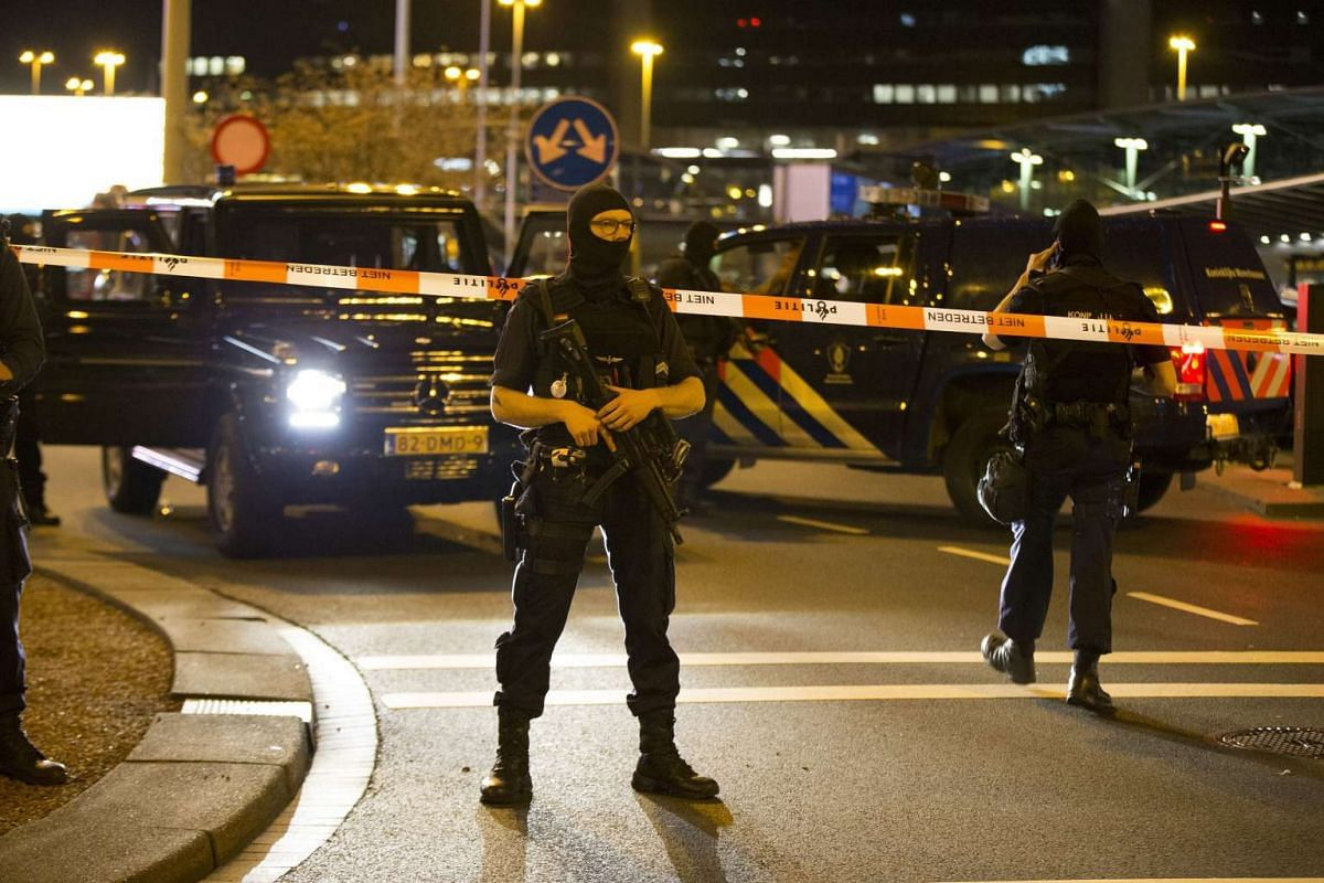 Dutch policemen stand guard by a cordoned off area outside Amsterdam's Schiphol Airport on April 12, 2016, after it was partially evacuated following a security alert. PHOTO: AFP