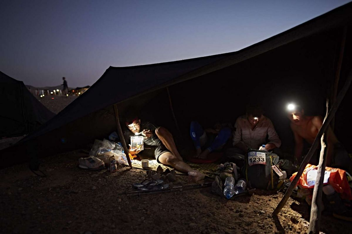 Competitors rest and eat at their bivouac during the 31st edition of the Marathon des Sables between Oued Moungarf and Ba Hallou in the southern Moroccan Sahara desert on April 12, 2016. PHOTO: AFP