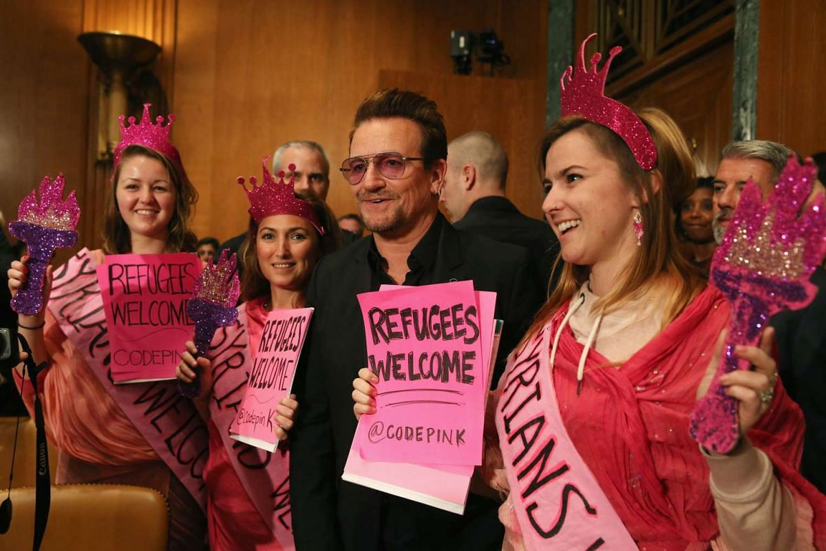 Bono, lead singer of the rock band U2 and co-founder of ONE, a non-profit, non-partisan advocacy organisation, with protesters before a Senate Appropriations Subcommittee hearing, on Capitol Hill on April 12, 2016, in Washington, DC. PHOTO: GETTY IMA