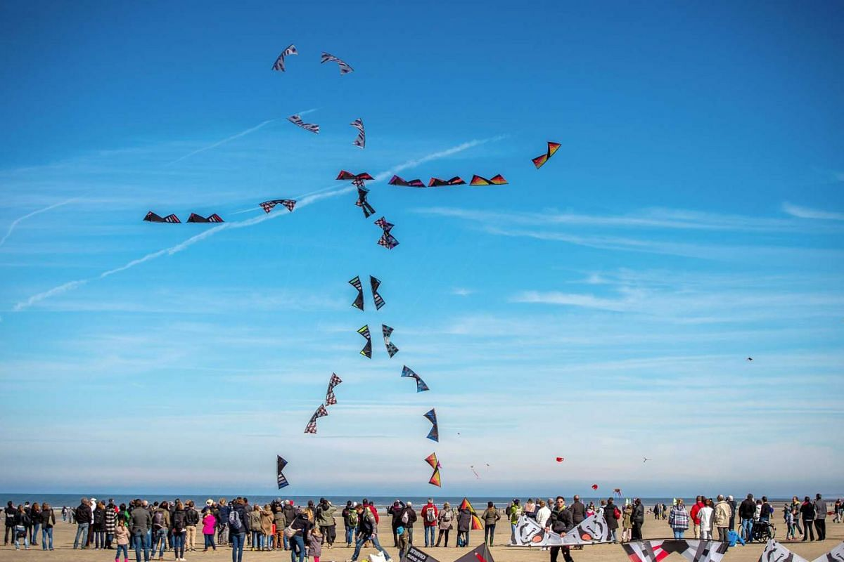 People fly kites during the 30th International Kite Festival in Berck-sur-Mer in northern France on April 12, 2016. PHOTO: AFP