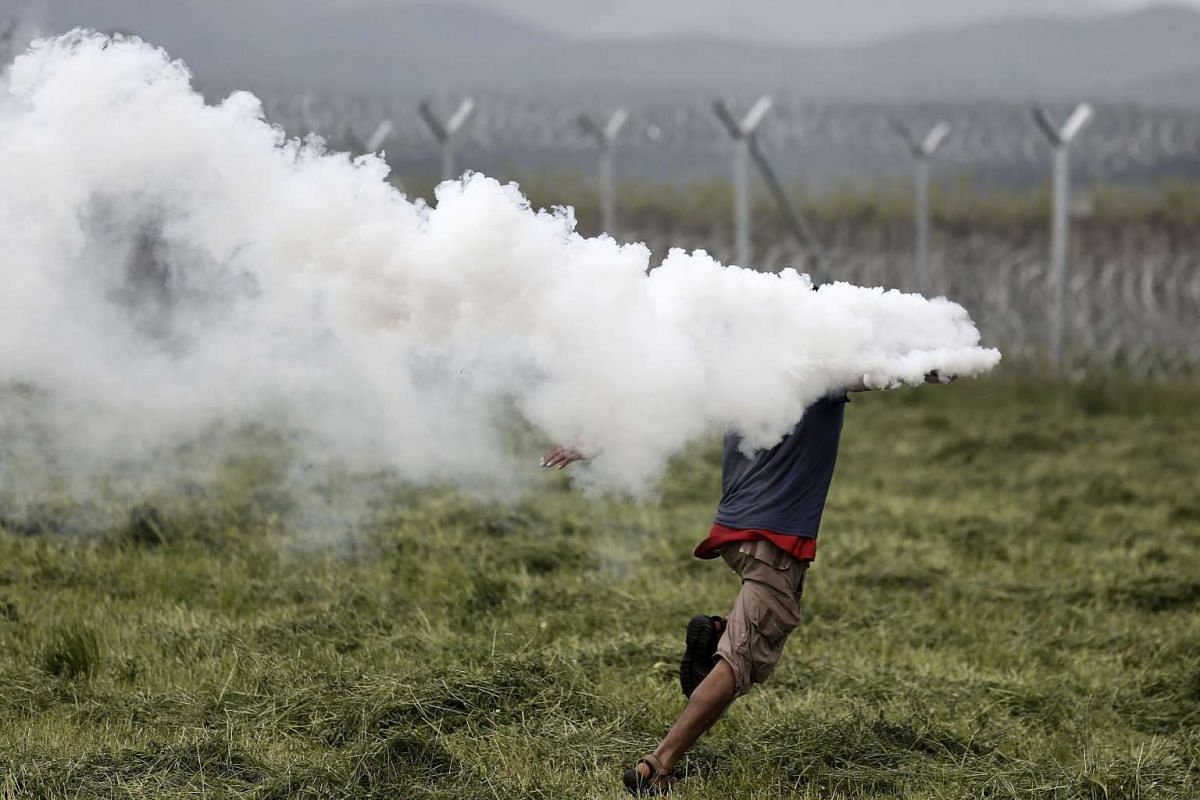 A refugee runs to throw back a tear gas canister at Macedonian police during a protest in which refugees were demanding the opening of the borders, near the refugee camp in Idomeni, on the border between Greece and the Former Yugoslav Republic of Mac