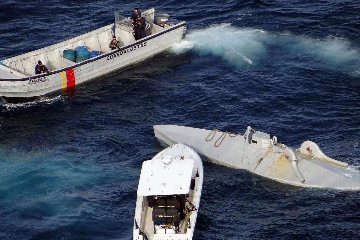 A handout photo released by Colombian Navy Force shows ships of Colombian Navy during the interception of a submersible (R) carrying six tons of cocaine on the sea border between Colombia and Ecuador, April 13, 2016. PHOTO: EPA/COLOMBIAN NAVY / HANDO