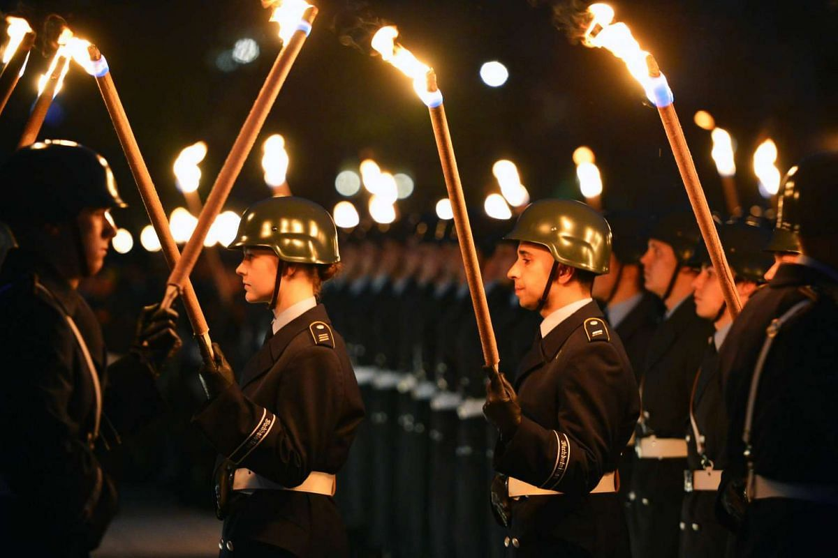 Members of the German armed forces hold a torchlight parade during US General Philip M Breedlove's farewell ceremony as Supreme Allied Commander Europe at the German defence ministry in Berlin on April 13, 2016. PHOTO: AFP