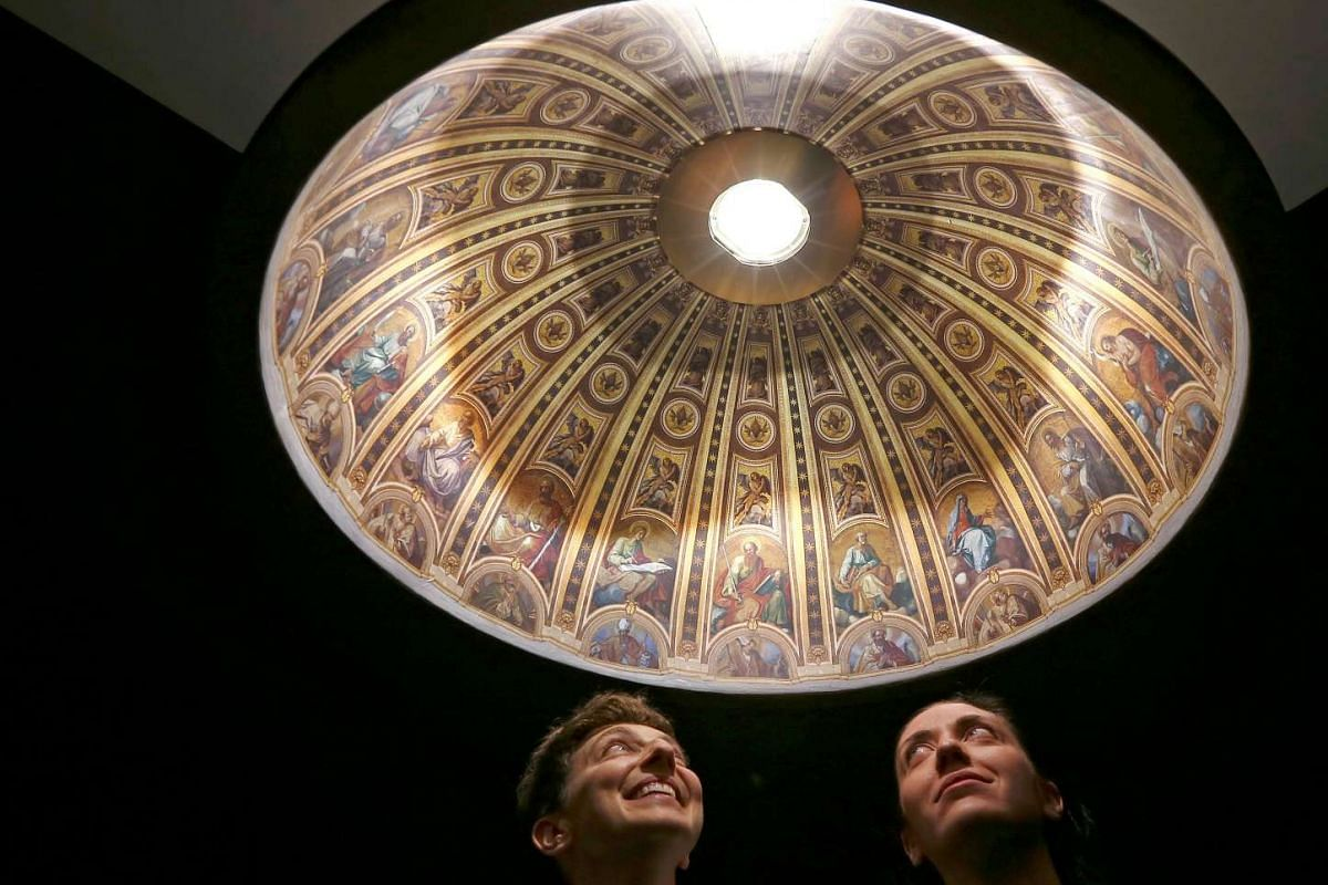 Italian designers Eleonora Barbareschi (L) and Alessandra Mantovani pose under their suspended lamp with a hyper-realistic reproduction of Saint Peter Basilica's dome at Milan Design Week April 13, 2016. PHOTO: REUTERS