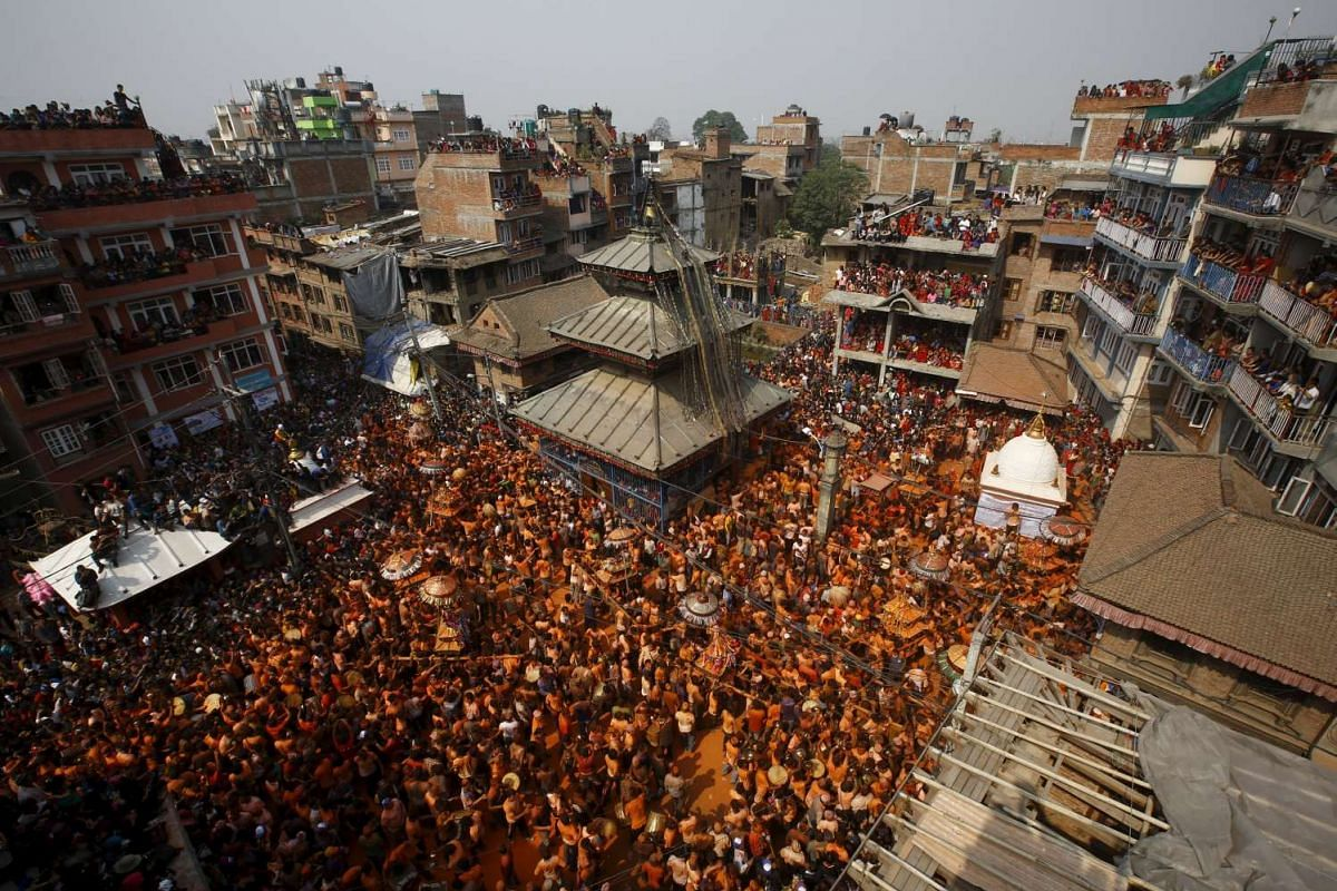 """Devotees covered in vermilion powder carry chariots as they circle the Balkumari Temple (centre) during the """"Sindoor Jatra"""" vermilion powder festival at Thimi, in Bhaktapur, Nepal, on April 14, 2016."""
