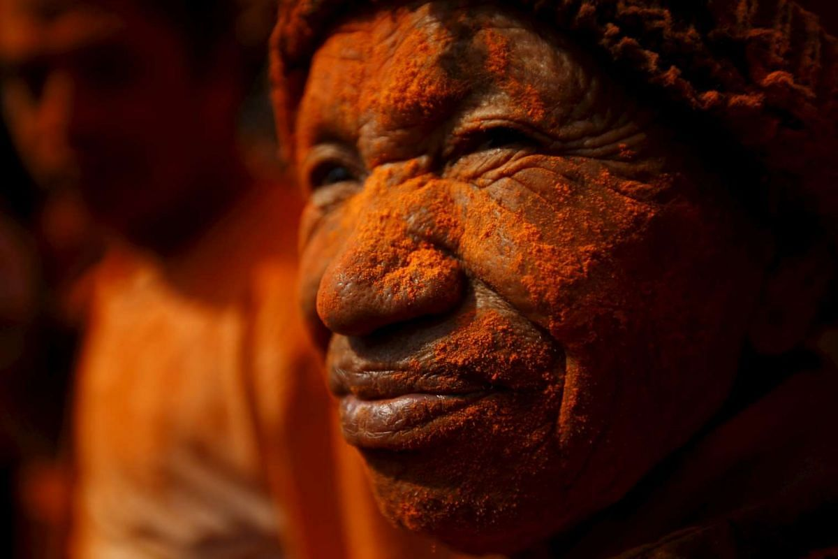 """A devotee is smeared in vermilion powder while celebrating the """"Sindoor Jatra"""" vermillion powder festival at Thimi, in Bhaktapur, Nepal, on April 14, 2016."""