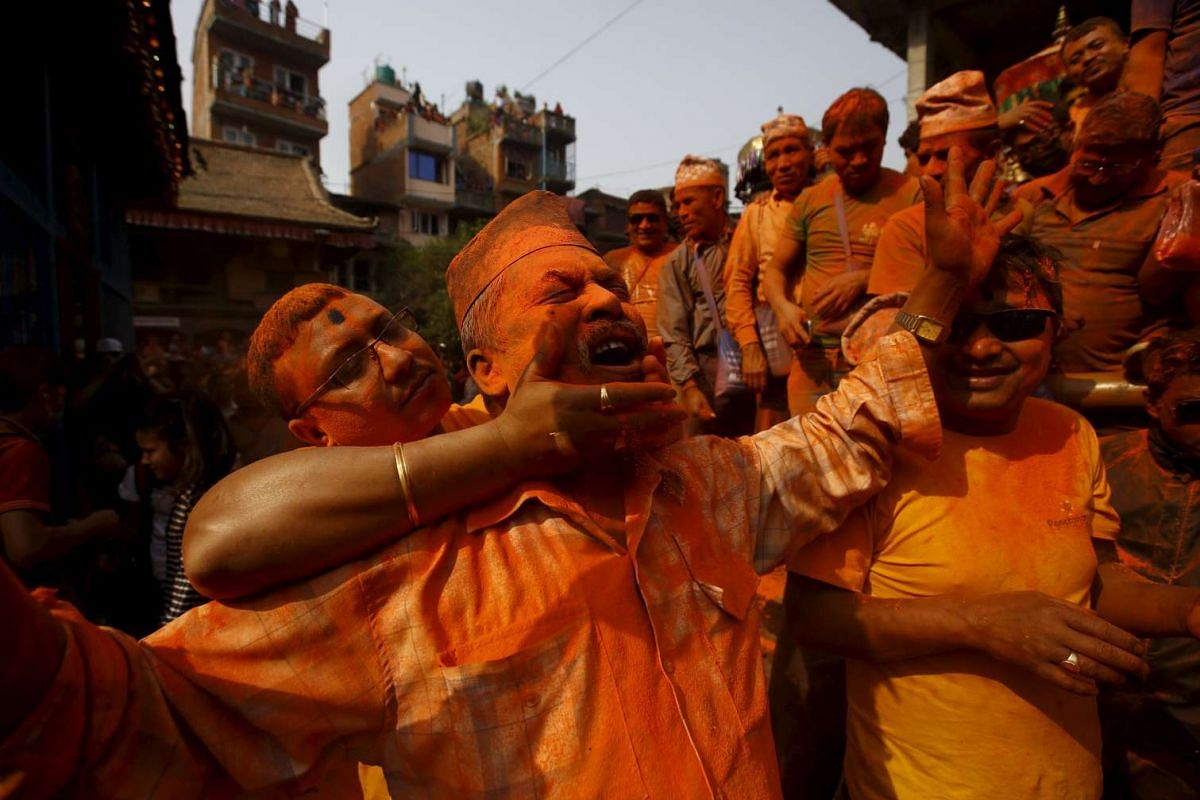 """A devotee is smeared with vermilion powder while celebrating the """"Sindoor Jatra"""" vermilion powder festival at Thimi, in Bhaktapur, Nepal, on April 14, 2016."""
