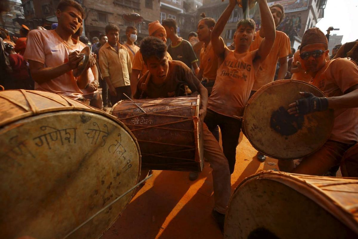 """Devotees play traditional musical instruments while celebrating the """"Sindoor Jatra"""" vermilion powder festival at Thimi, in Bhaktapur, Nepal, on April 14, 2016."""