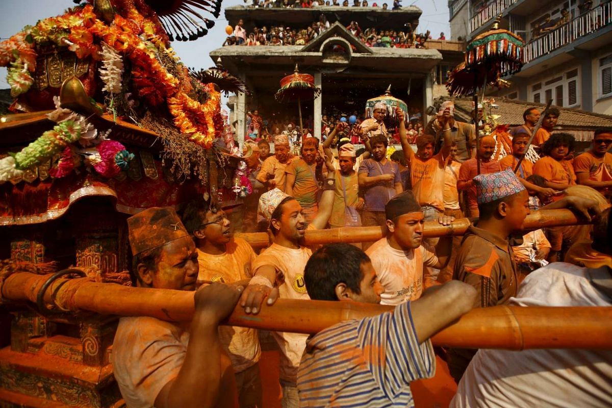 """Devotees carry a chariot as they celebrate the """"Sindoor Jatra"""" vermilion powder festival at Thimi, in Bhaktapur, Nepal, on April 14, 2016."""