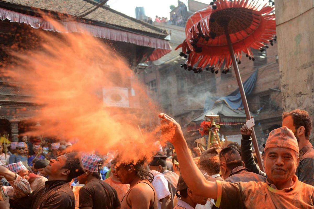 Nepalese revellers toss vermilion powder during The Bisket Jatra Festival at Thimi, on the outskirts of Kathmandu, on April 14, 2016.