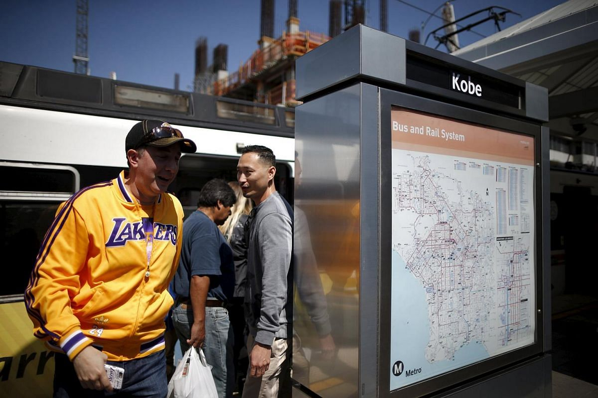 Lakers fans on a train platform renamed in honour of Los Angeles Lakers' guard Kobe Bryant near Staples Center on April 13, 2016.