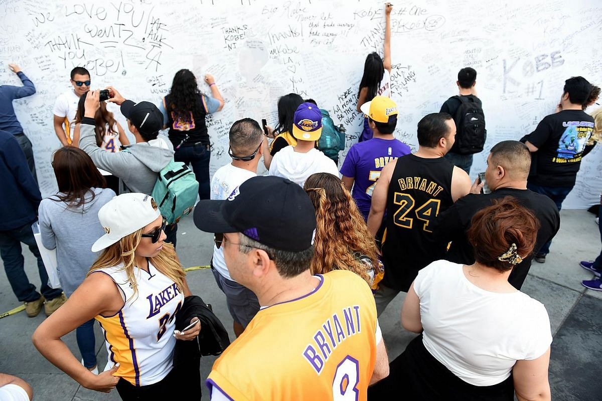 Fans sign an autograph board before Kobe Bryant of the Los Angeles Lakers plays the final game of his career on April 13, 2016.