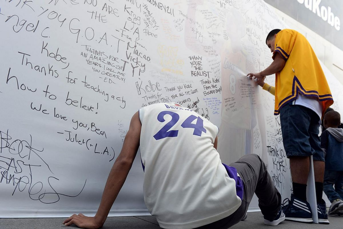 Fans sign a large greeting card for Los Angeles Lakers player Kobe Bryant in front of Staples Center.