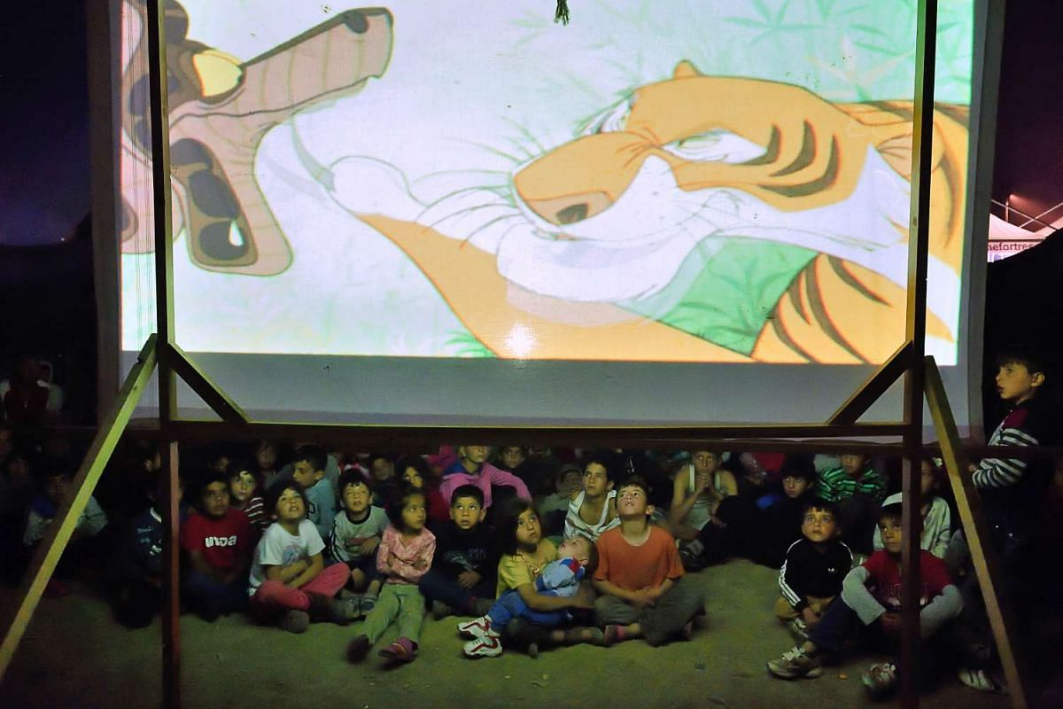 Refugee children watch a cartoon at the makeshift camp of the Greek-Macedonian border near the village of Idomeni, on April 14, 2016. PHOTO: AFP