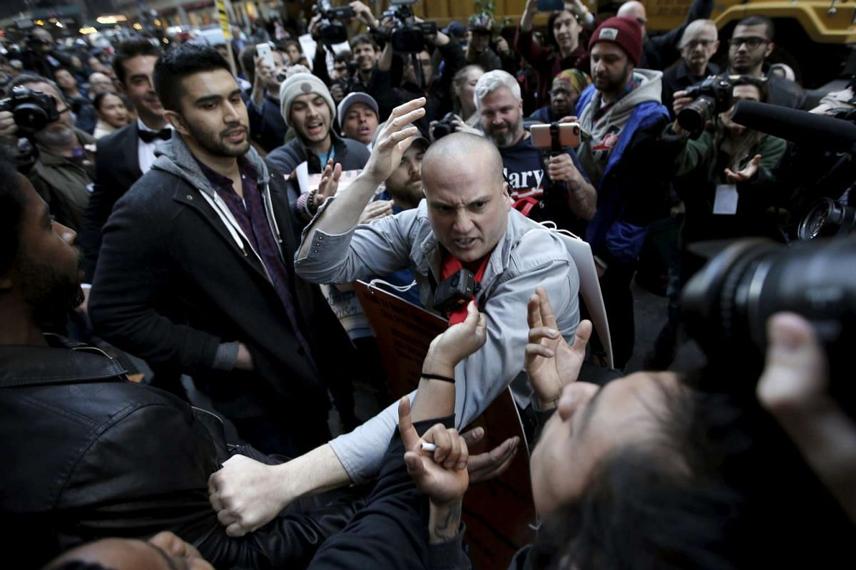 A supporter of Republican U.S. presidential candidate Donald Trump (C) fights with protesters demonstrating against Donald Trump in midtown Manhattan in New York City, April 14, 2016. PHOTO: REUTERS