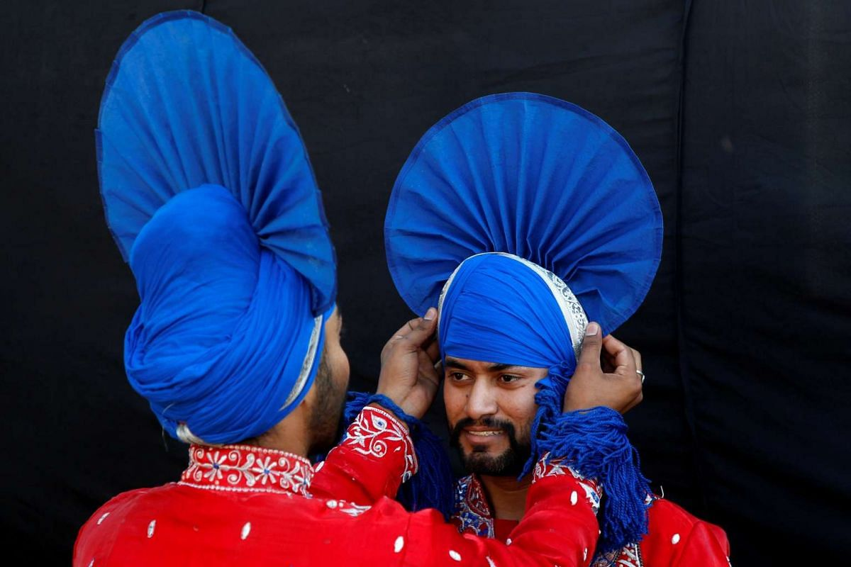 A folk dancer adjusts the headgear of a companion as they wait to perform during Baisakhi celebrations in Chandigarh, India April 14, 2016. PHOTO: REUTERS