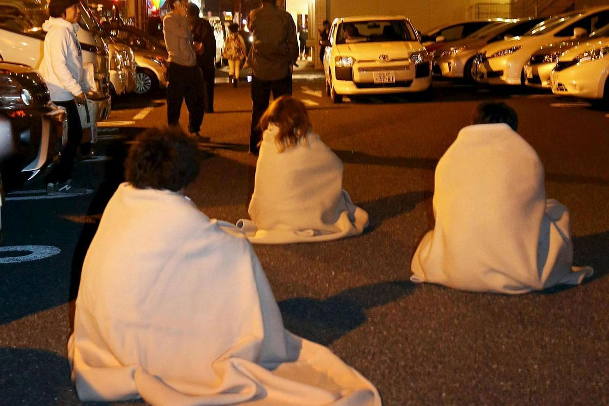 People wrapped in blankets sit on the road as they are evacuated from a hotel after an earthquake in Kumamoto, Japan, on April 14, 2016.