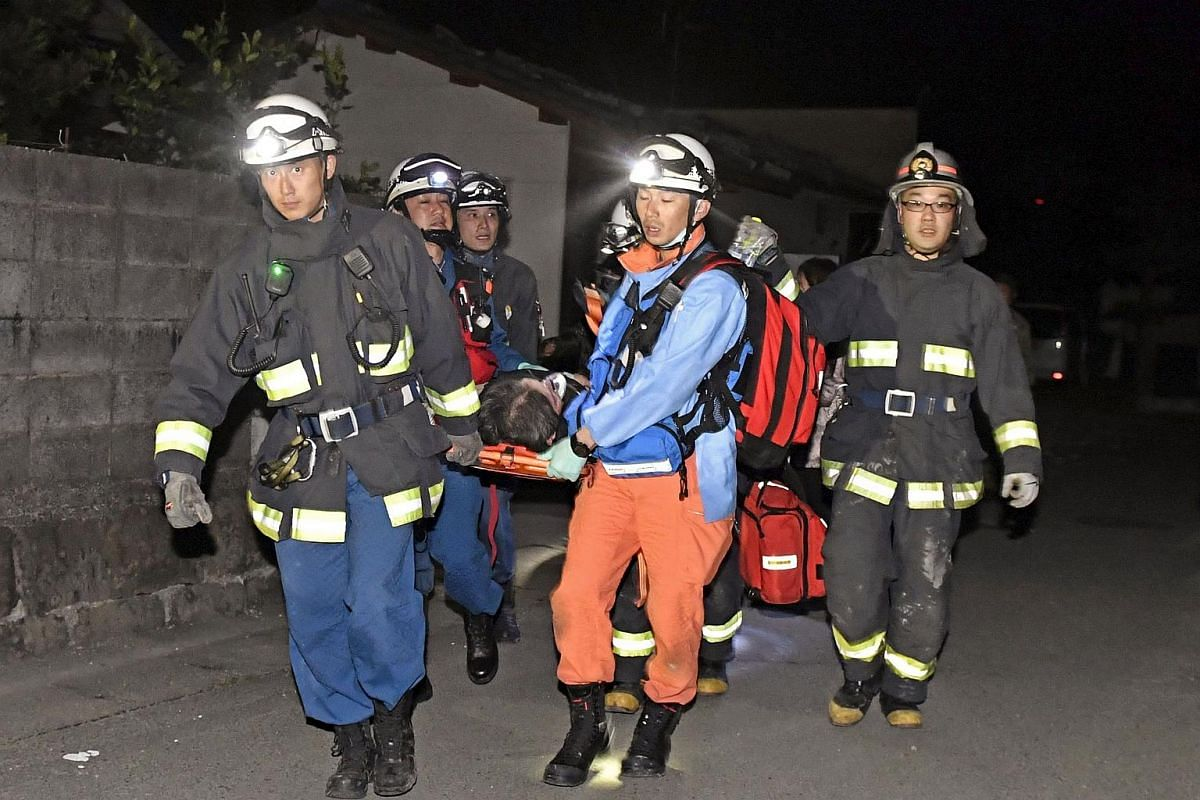 Rescue workers use a stretcher to carry a man rescued from a collapsed house in Mashiki town, Kumamoto, Japan, on April 15, 2016.