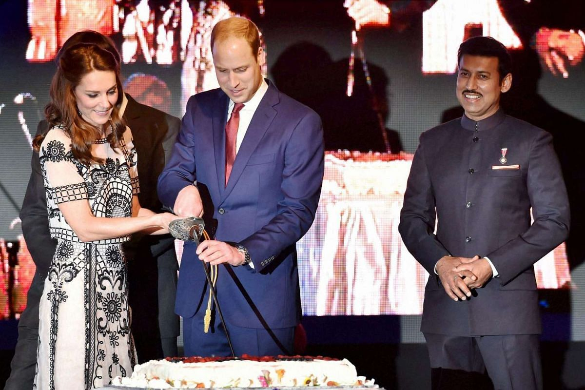 Prince William, Duke of Cambridge, and Catherine, Duchess of Cambridge, cut a cake during 90th birthday celebrations for Queen Elizabeth II, as India's Minister for Information and Broadcasting Rajyavardhan Singh Rathore looks on, in New Delhi, on Ap