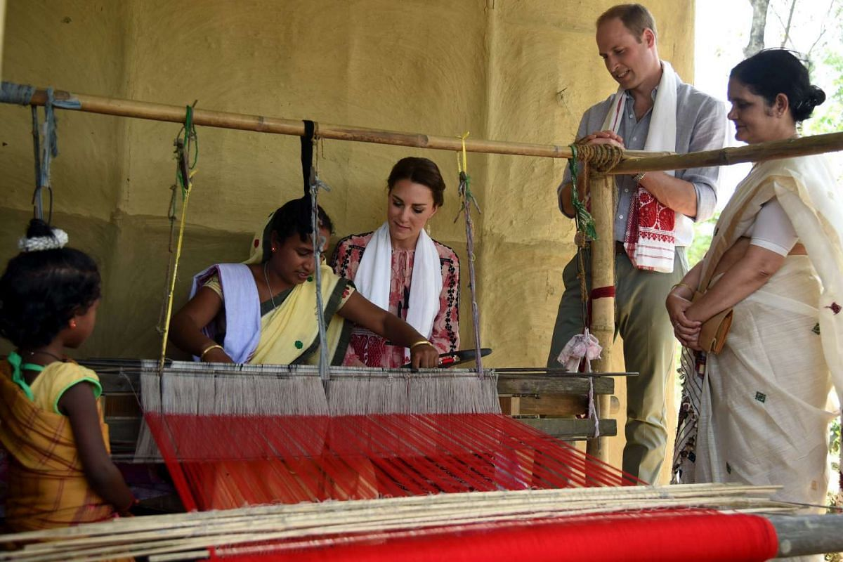An Indian woman presents a handloom cloth to Catherine, Duchess of Cambridge, as Prince William, Duke of Cambridge, looks on in Panbari village in Kaziranga, India, on April 13, 2016.