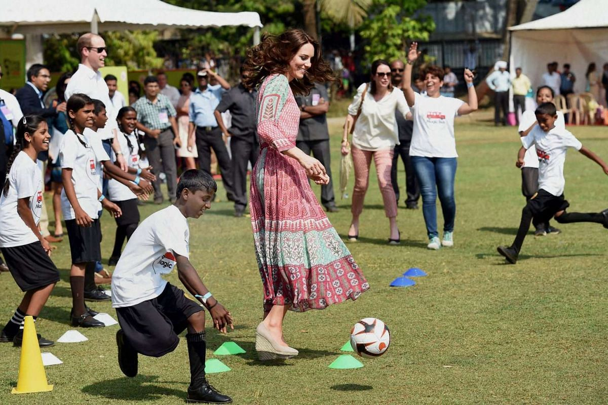 Catherine, Duchess of Cambridge, is watched by Prince William, Duke of Cambridge, as she takes part in games with Indian children, on April 10, 2016.