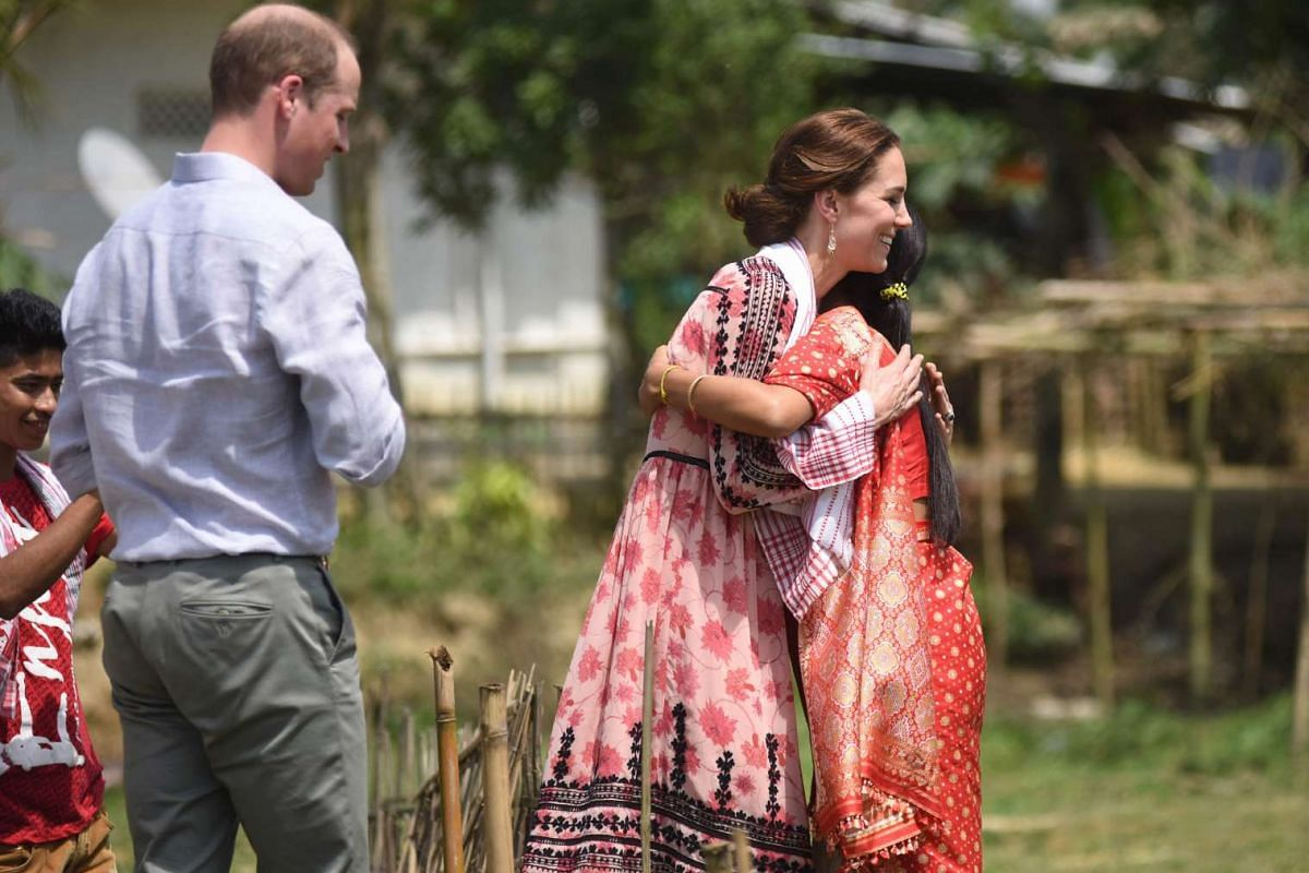 Catherine, Duchess of Cambridge, is greeted by an Indian resident as Prince William, Duke of Cambridge, looks on during a visit to a village tea garden in Kaziranga, India, on April 13, 2016.