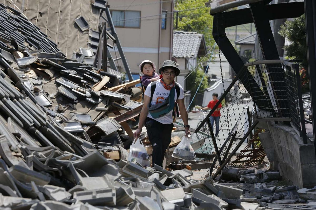A resident carrying his child on his back walks through debris of collapsed houses with supplies in the town of Mashiki, Kumamoto, Japan, on April 15, 2016.