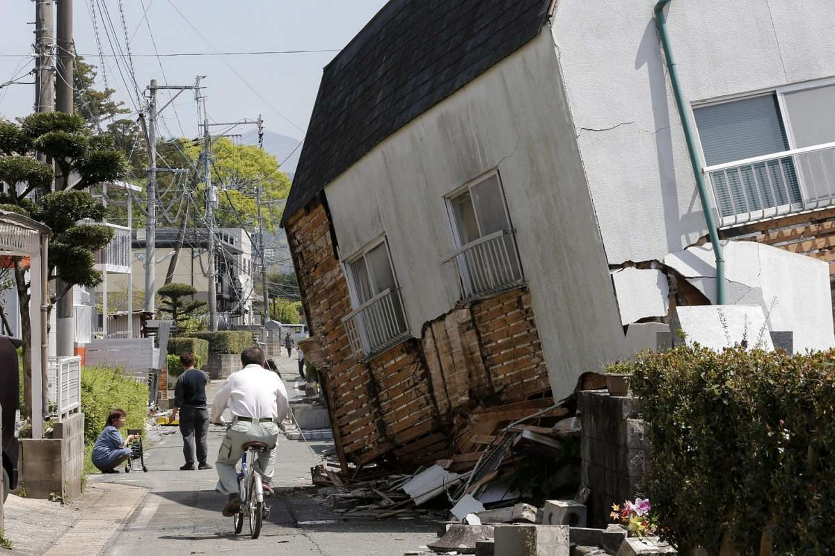 A man cycles past a collapsed house on a street in Mashiki town, Kumamoto, Japan, on April 15, 2016.