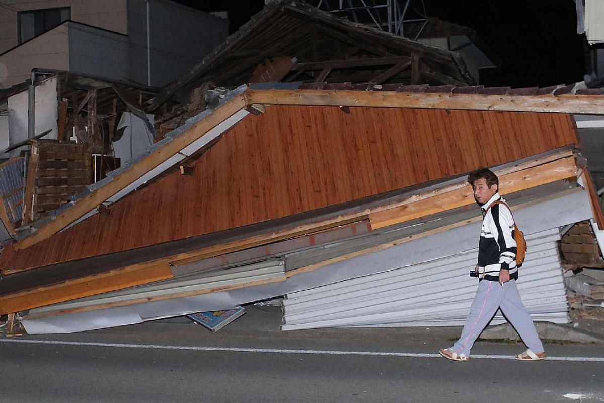 A resident walks in front of a collapsed house in the town of Mashiki, Kumamoto, Japan, on April 15, 2016.