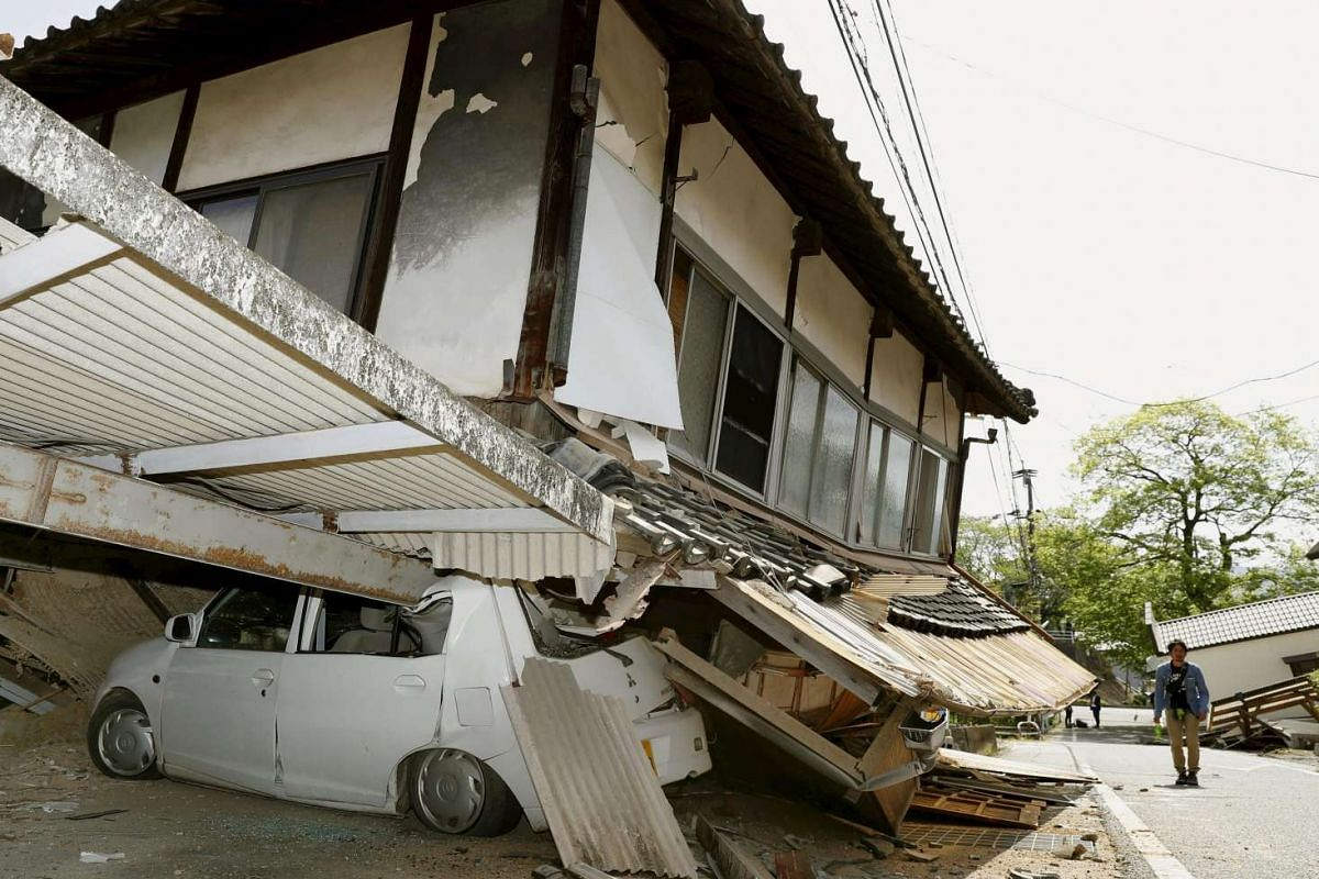 A man walks near a damaged house and car caused by an earthquake in Mashiki town, Kumamoto, Japan, on April 15, 2016.
