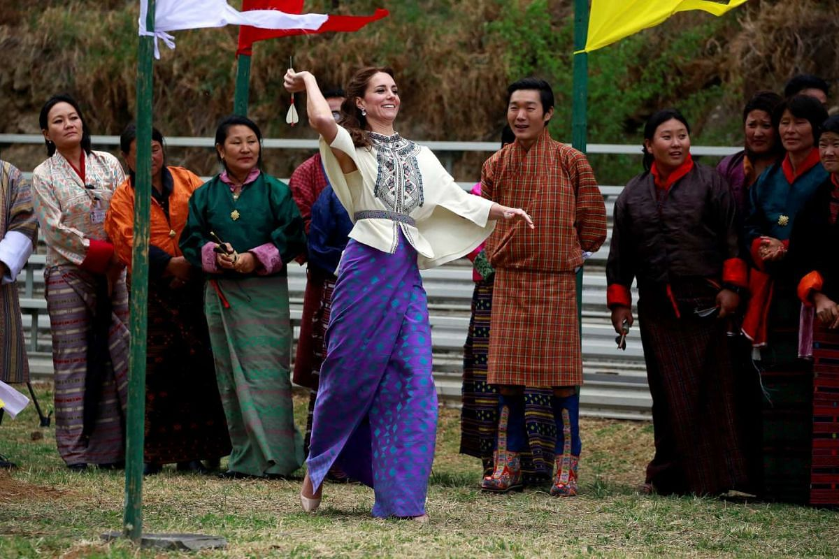 Britain's Catherine, Duchess of Cambridge, throws a dart while taking part in the traditional game of Khuru at Changlimithang Archery Ground, on April 14, 2016.